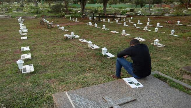 Un hombre llora por un familiar fallecido por COVID-19, en un cementerio en Brasilia (Brasil).