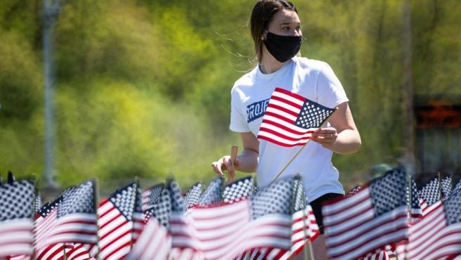 Una voluntaria coloca una de las más de 2.500 banderas plantadas en Foxborough, Massachusetts (EE UU) para recordar a los fallecidos por el coronavirus en la ciudad.