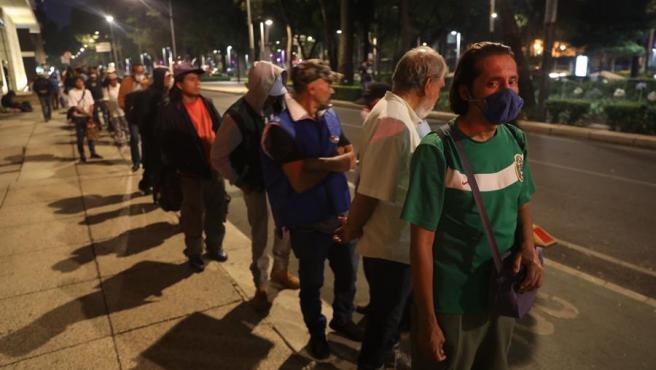 Personas sin recursos y especialmente afectadas por la pandemia del coronavirus hacen cola para recibir alimentos en Ciudad de México.