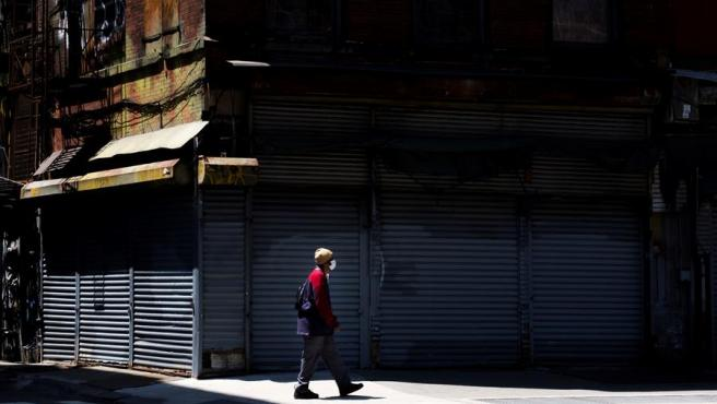 Un hombre con una mascarilla camina frente a negocios cerrados por la pandemia del coronavirus, en Nueva York.