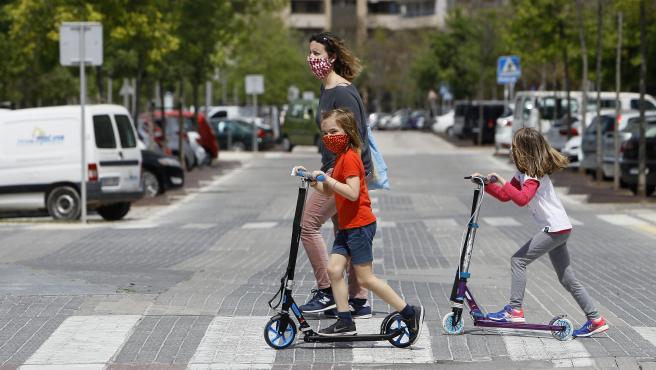 Dos niñas con mascarilla cruzan un paso de peatones montadas en patinete.