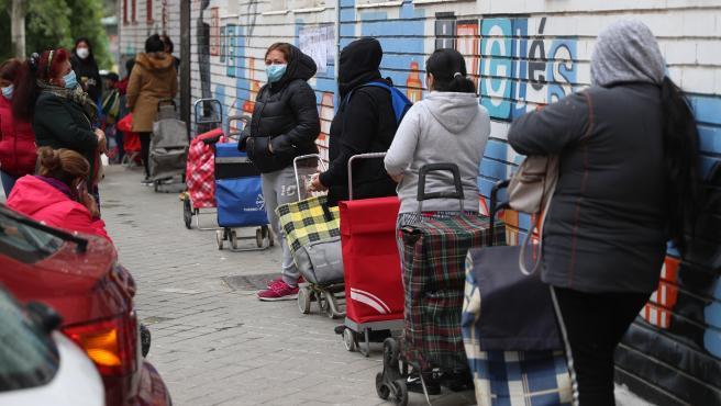 Varias personas esperan en la fila para recoger alimentos proporcionados por la Asociación de vecinos de Aluche, debido a la difícil situación de muchas familias de Aluche provocada por la pandemia.