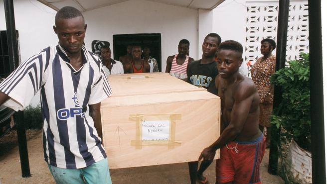 El ataúd con los restos de Miguel Gil es trasladado por trabajadores de la morgue de Freetown en mayo de 2000.