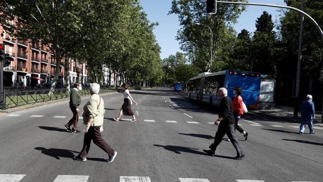 Varias personas cruzan por un punto del Paseo de la Castellana de Madrid.