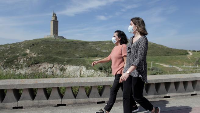 Dos mujeres con mascarilla caminan por el entorno de la Torre de Hércules, en A Coruña.