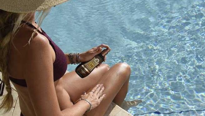 Una joven en una piscina se aplica protección solar con bronceador.