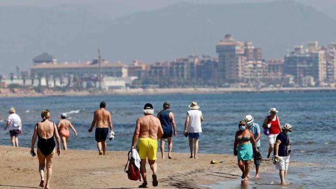 Varias personas disfrutan del buen tiempo y del calor en la playa de la Malvarrosa.
