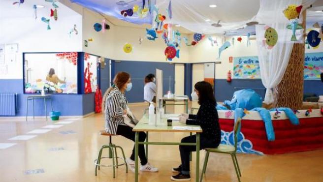 Una administrativa de la Escola l'Estel de Barcelona atiende a una persona durante la preinscripción escolar el pasado 19 de mayo en los colegios e institutos de Cataluña