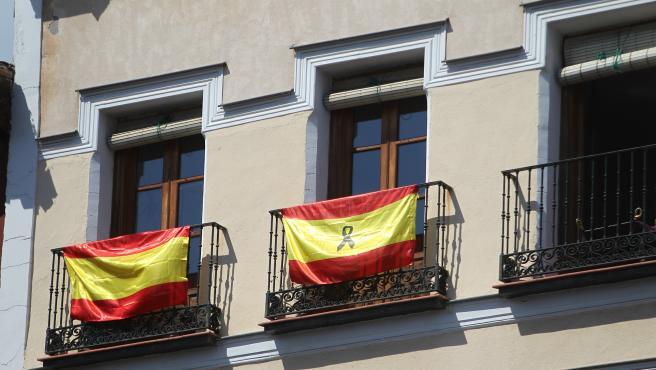 Dos banderas de España en los balcones, una de ellas con crespón negro.