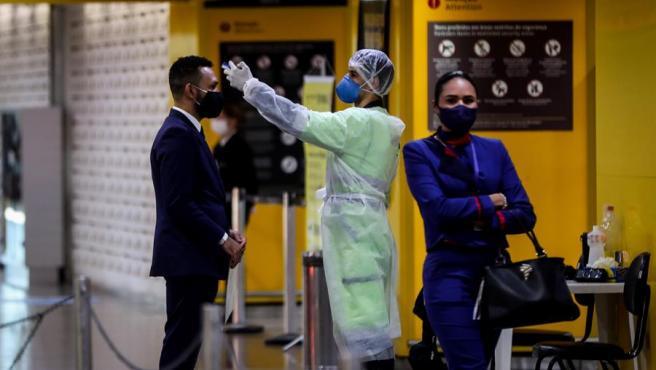 Un trabajador sanitario toma la temperatura a un pasajero para detectar síntomas de COVID-19, en la zona de embarque del aeropuerto internacional de Guarulhos, en Sao Paulo (Brasil).