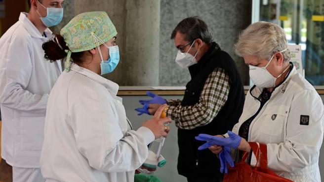 Sanitarios toman la temperatura a dos personas para detectar posibles síntomas de COVID-19, antes de acceder al Hospital de Alcorcón, en Madrid.