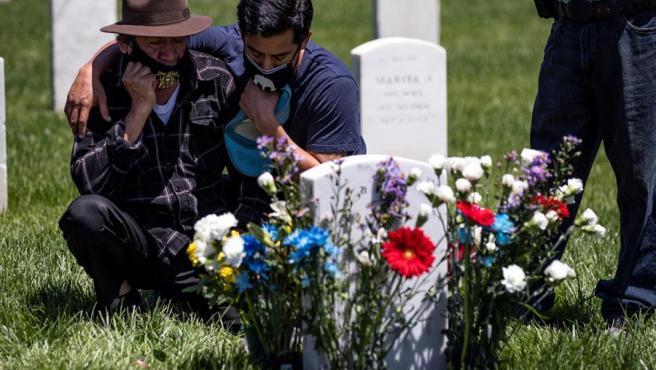 Un hombre con mascarilla por la pandemia del coronavirus visita con su hijo la tumba de su otro hijo en el Cementerio Nacional de Los Ángeles, EE UU, en el Día de los Caídos.