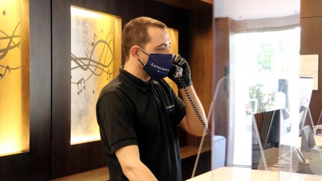 Pla mitjà d'un empleat de l'hotel Catalonia Rigoletto, a Barcelona, agafant el telèfon. Imatge del 25 de maig de 2020. (Horitzontal)