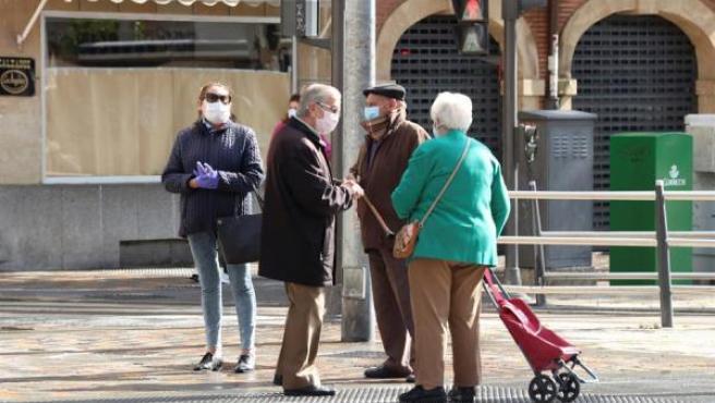 Varias personas mayores aprovechan para conversar mientras esperan para entrar en una sucursal bancaria en Salamanca.