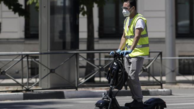 Un hombre protegido con mascarilla monta en un patinete eléctrico