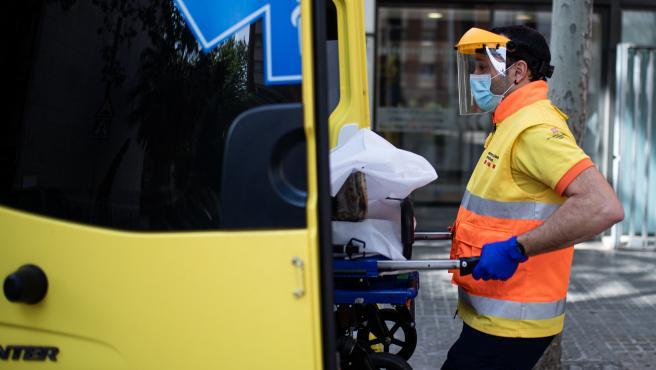 Un técnico del Sistema de Emergencias Médicas (SEM) de la Generalitat de Cataluña mete una camilla en una ambulancia durante un servicio y limpieza de EPIs, en Barcelona/Catalunya (España) a 19 de abril de 2020 (archivo).
