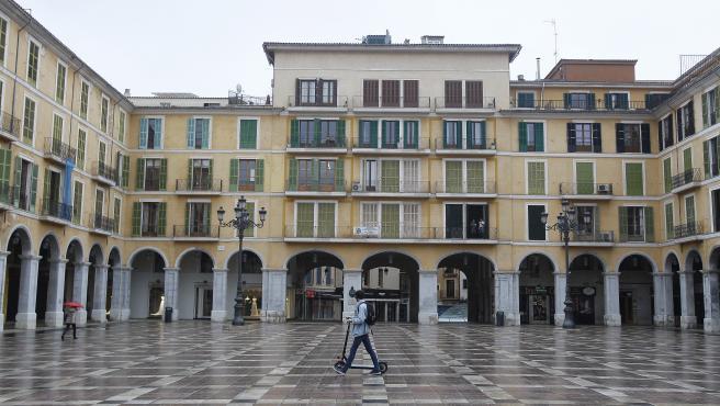 Un transeúnte cruza la Plaza Mayor vacía durante el primer día laborable del estado de alarma.