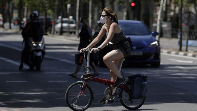 Una mujer protegida con mascarilla monta en una bicicleta