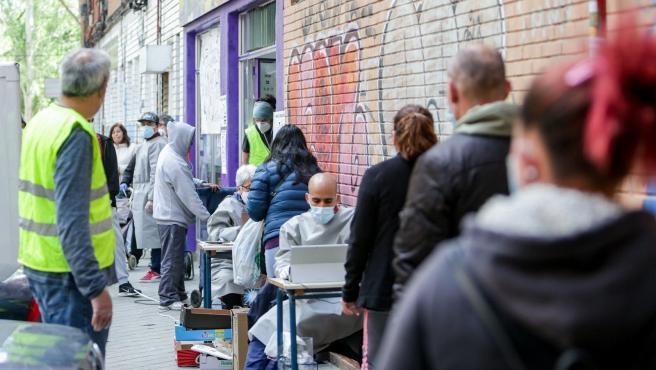 Cientos de personas sin recursos hacen cola en Aluche en busca de 'una bolsa de comida'.
