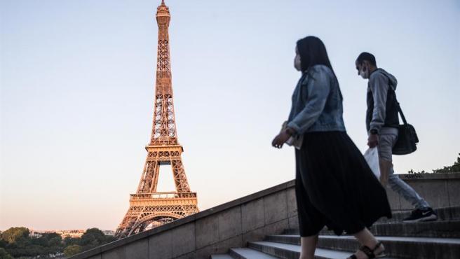 Dos personas con mascarillas por la pandemia del coronavirus caminan cerca de la Torre Eiffel, en París, Francia.