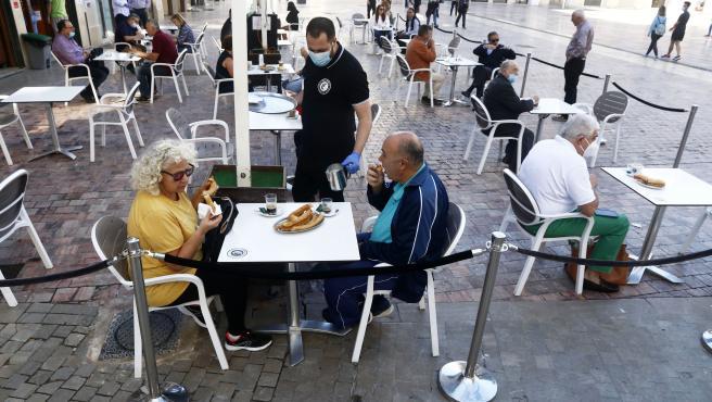 MLG 18-05-2020.-Primeros clientes disfrutan de las terrazas de las cafetería ede Málaga en la primera jornada de la Fase 1, en la imagen la cafetería Café Central en la plaza de la Constitución.-ÁLEX ZEA.