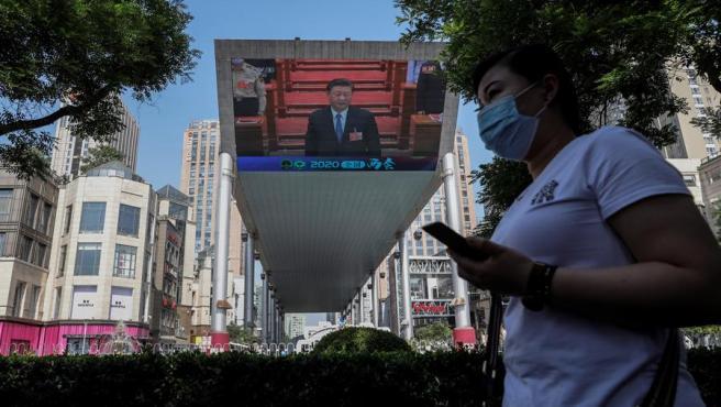 Una mujer con mascarilla por la pandemia del coronavirus pasa junto a una pantalla gigante en la que se retransmite el discurso del presidente chino, Xi Jinping, durante la clausura de la Asamblea Nacional Popular, en Pekín.