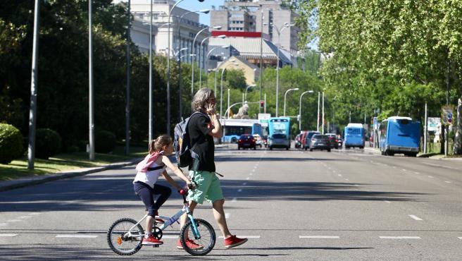 Un hombre y una niña en bicicleta pasean por Madrid en fase 1.