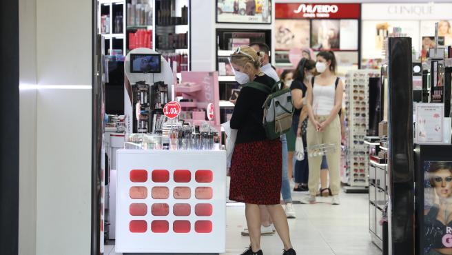 Varias personas con mascarilla en una perfumería abierta en el primer día de la fase 1 en Madrid.