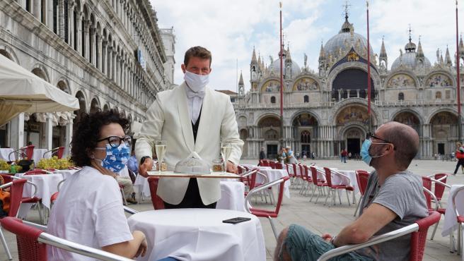 Un camarero sirve a dos turistas en la plaza de San Marcos en Venecia (Italia).