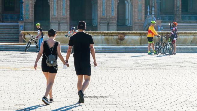 Una pareja cogidos de la mano en la Plaza de España, en Sevilla (Andalucía, España), a 03 de mayo de 2020 (archivo).