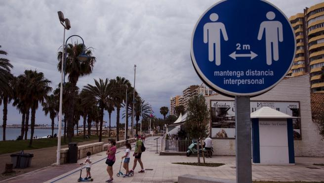 Una familia en el paseo marítimo de la Malagueta ante una señal que recuerda mantener la distancia de 2 metros entre personas.