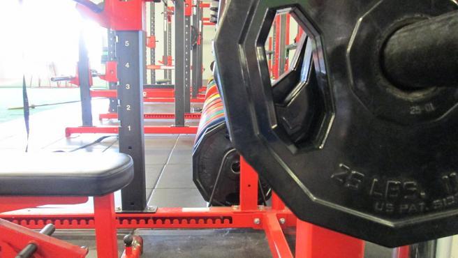 un entrenamiento de fuerza puede realizarse con mancuernas, barras o máquinas.