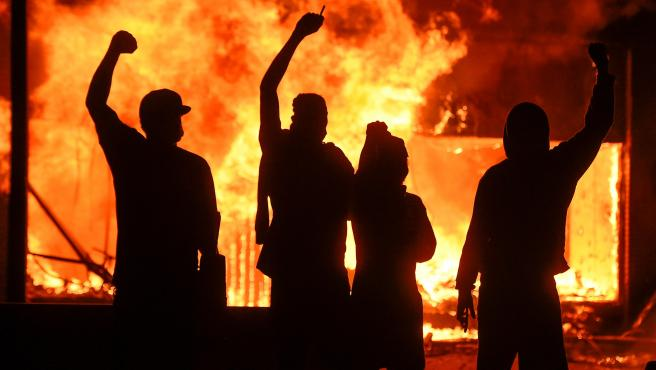 Un grupo de manifestantes, ante un comercio en llamas en Minneapolis.