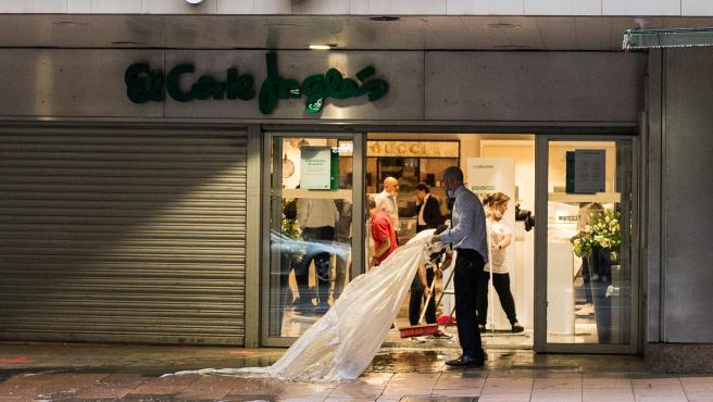 Trabajadores de El Corte Inglés de la calle Goya realizan labores de limpieza y expulsión de agua debido a la fuerte lluvia caída en Madrid.