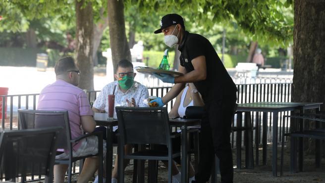 Un camarero protegido con mascarilla atiende a una mesa de una terraza.