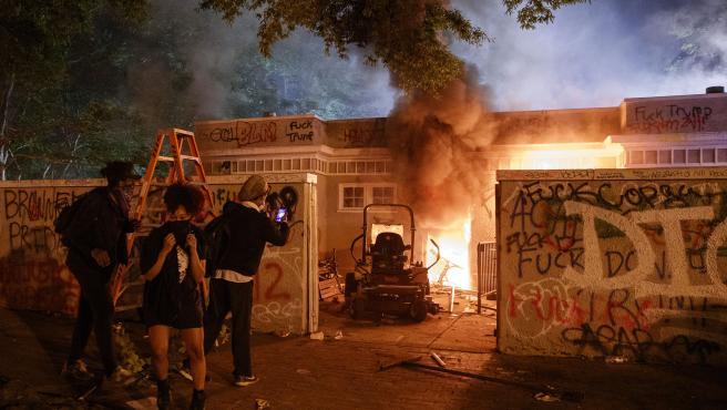 Tres manifestantes graban con un móvil como arde una casa, en una barrio de Washington DC (EE UU), durante una violenta protesta por la muerte del afroamericano George Floyd.