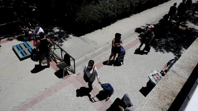 Colas de personas esperan a las puertas de la Parroquia Santa María Micaela para recibir una ayuda alimentaria. En Madrid (España), a 29 de mayo de 2020.