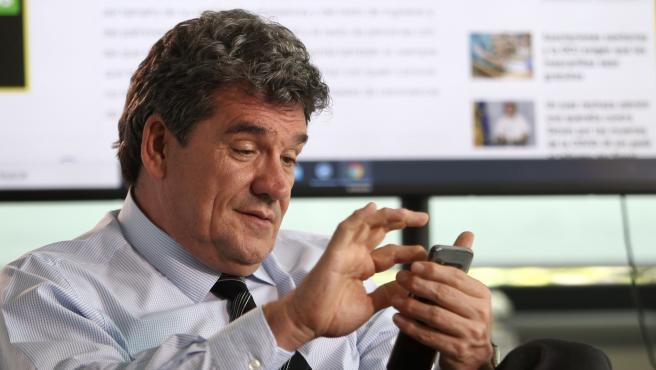 El ministro José Luis Escrivá consulta el móvil, durante el encuentro digital en 20minutos.