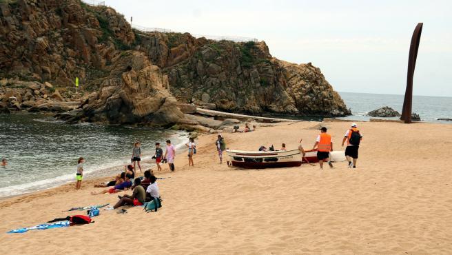 Playa de Blanes con bañistas e informadores explicando las medidas de seguridad.