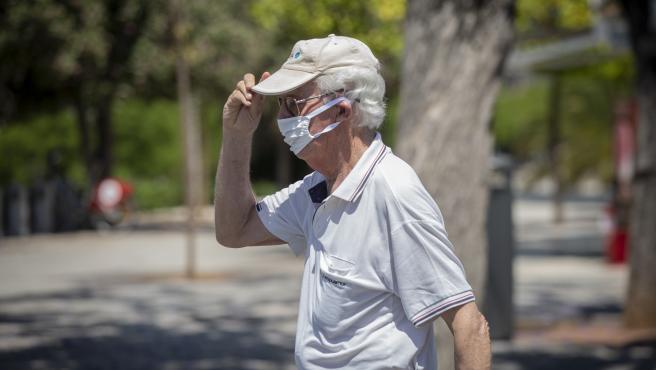 Un hombre con mascarilla y gafas de sol se coloca una gorra durante un 'episodio de altas temperaturas'. Según la calificación de la Agencia Estatal de Meteorología (AEMET). En Sevilla,(Andalucía, España), a 22 de mayo de 2020.