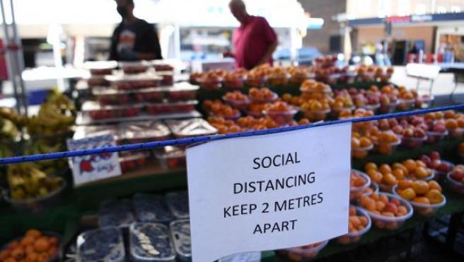Un aviso de distanciamiento social en un mercado al aire libre en Londres, Gran Bretaña.
