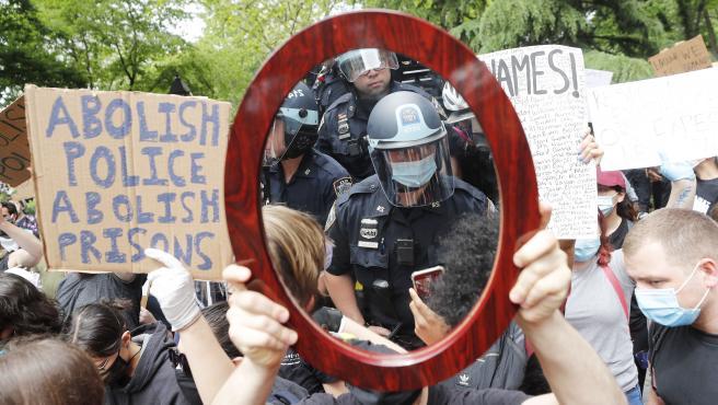 Policías se reflejan en un espejo sostenido por un manifestante durante una protesta en Nueva York por la muerte de George Floyd.