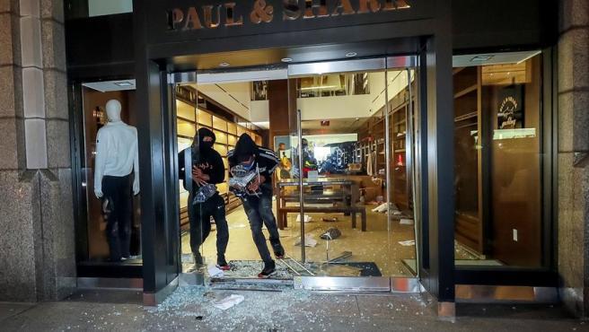Dos encapuchados saquean una tienda en Madison Avenue, en Manhattan (Nueva York), durante los disturbios por la muerte a manos de la Policía del afroamericano George Floyd.