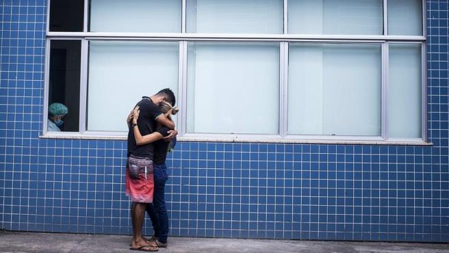 Dos personas se abrazan junto a una sala de un hospital dedicada a tratar pacientes indígenas de COVID-19, en Manaos, en el estado brasileño de Amazonas.