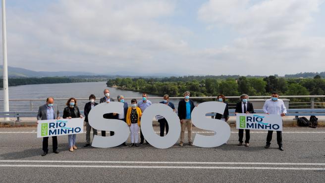 doce concellos del Miño en la provincia de Pontevedra y del norte de Portugal sostienen varias pancartas en la protesta simbólica conjunta en el Puente de la Amistad, que une la localidad pontevedresa de Tomiño y la portuguesa Vilanova da Cerveira.