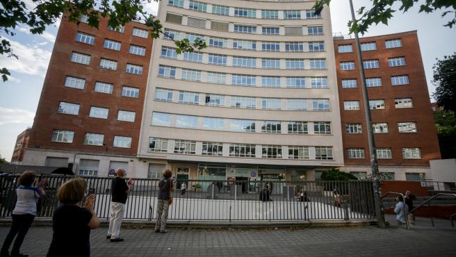 Sanitarios y varios transeúntes aplauden en la puerta del Hospital Fundación Jiménez Díaz.