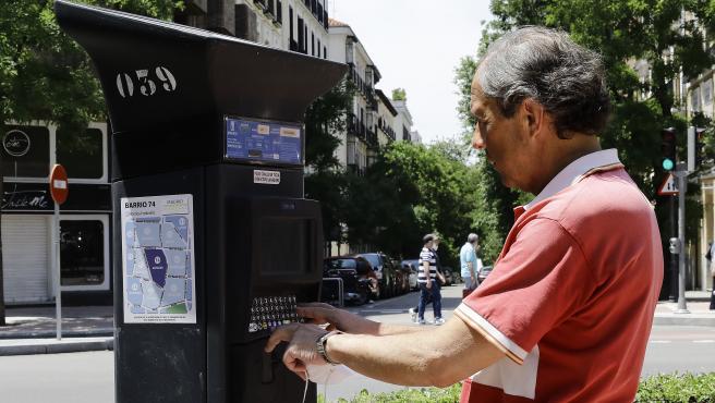 Un hombre utiliza el parquímetro del Servicio de Estacionamiento Regulado (SER) de Madrid