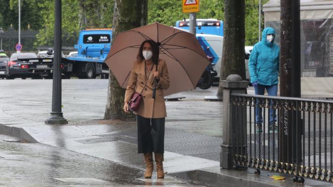 Una mujer con paraguas en Madrid en un día de lluvia y bajada de temperaturas en toda España, en que en gran parte de la Península y Baleares se espera nubosidad, con chubascos y tormentas casi generalizados,