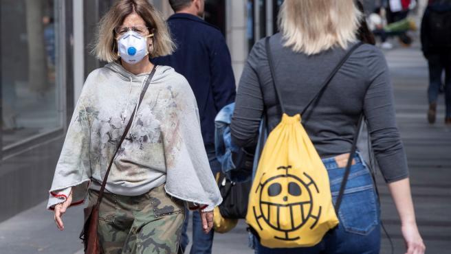 Un mujer se protege del coronavirus con una mascarilla en la Gran Vía de Murcia.