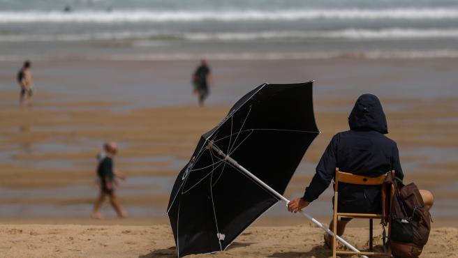 Un joven se protege este sábado en la playa de la Zurriola de San Sebastián.